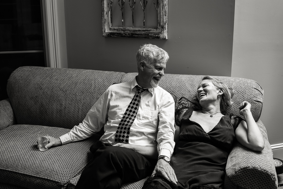 Middle aged couple relaxing on couch during wedding reception.