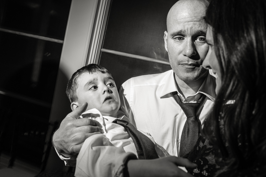 Sad boy in father's arms at wedding reception.