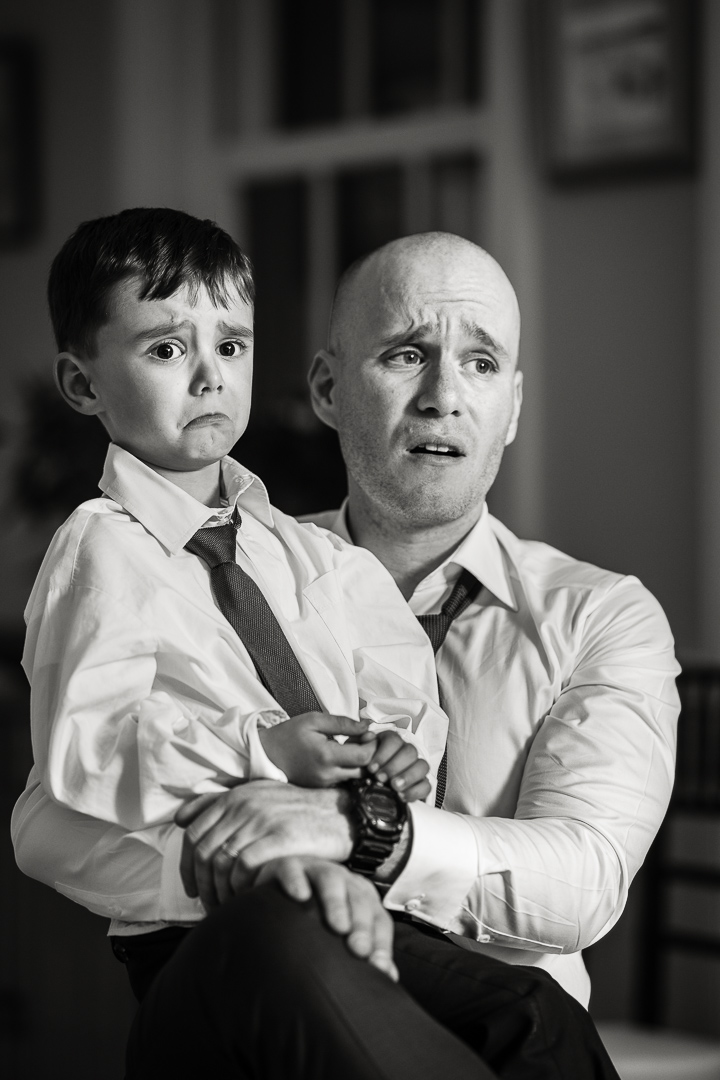 Man and son at wedding, sharing identical expression.