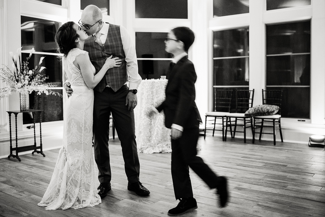 wedding couple kiss at end of evening with son entering frame by Colorado wedding photojournalist