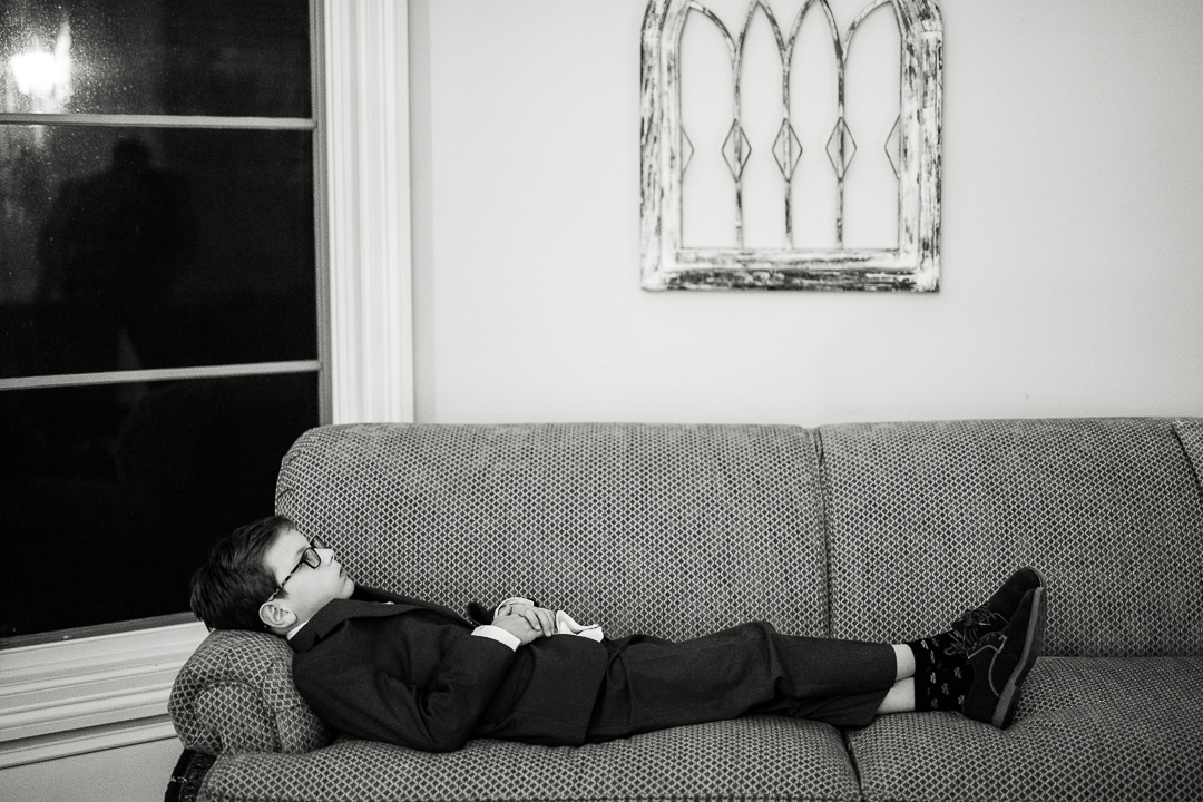 bored boy sits on couch during wedding reception